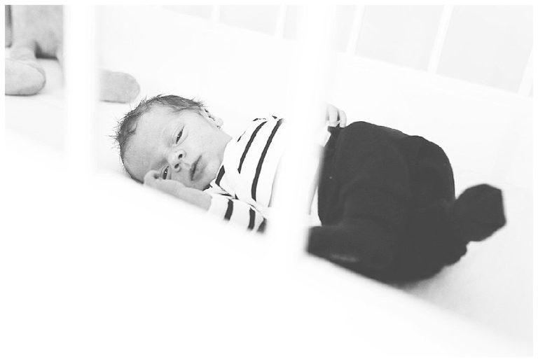 zwart wit foto van newborn baby james in wiegje