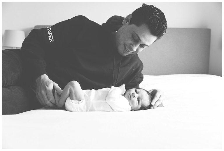 Vader knuffelt met newbornbaby op bed tijdens de newbornshoot Den Haag.