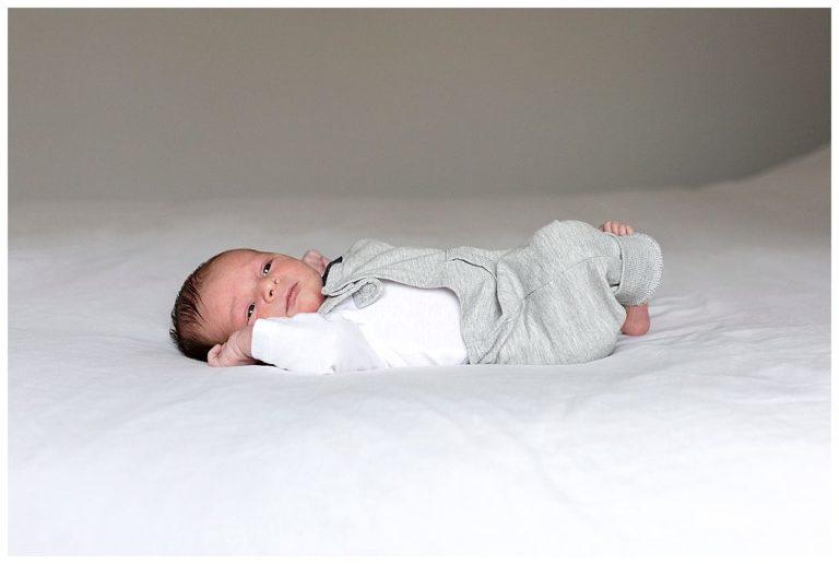 Newbornshoot Den Haag van een kleine baby liggend op bed van zijn ouders/