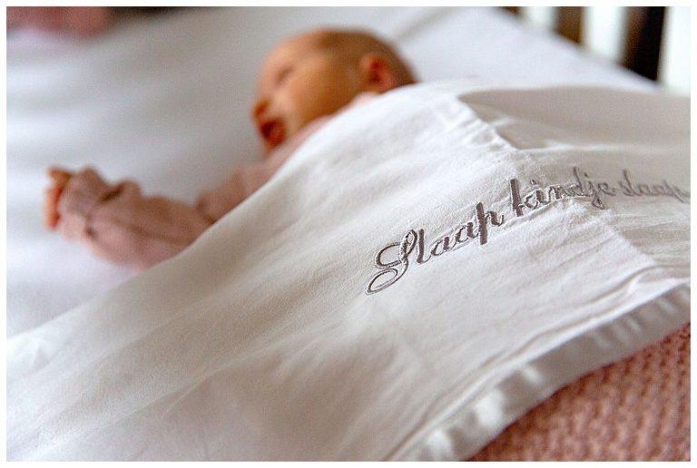 newbornfotografie in bussum van baby meisje dat onder een dekentje ligt