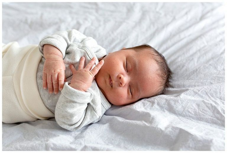 Slapende newborn met gevouwen handjes op bed van de ouders.
