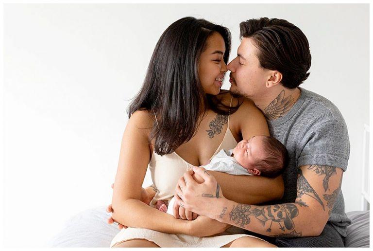 Trotse ouders kussen elkaar kijken terwijl de moeder haar newborn vasthoudt.