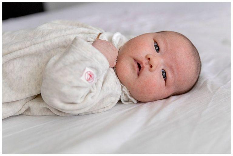 Baby liggend op bed  die naar de camera kijkt.