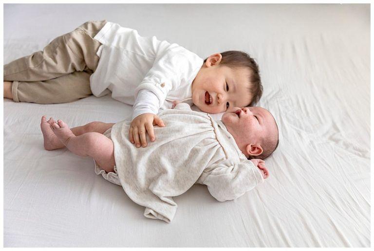 Grote broer kietelt baby zusje op bed.