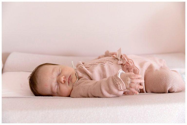 Baby meisje in roze pakje slaapt in wiegje