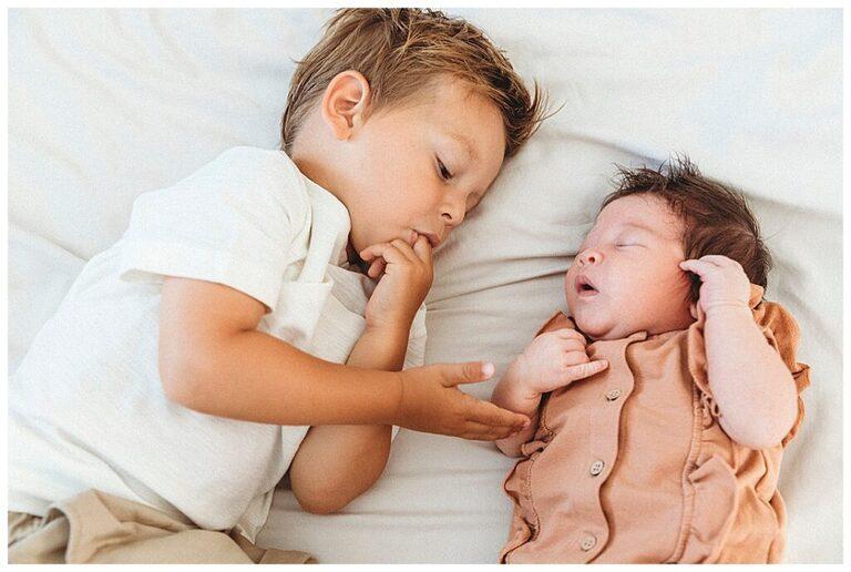 Peuter houdt de hand van zijn pasgeboren zusje vast.